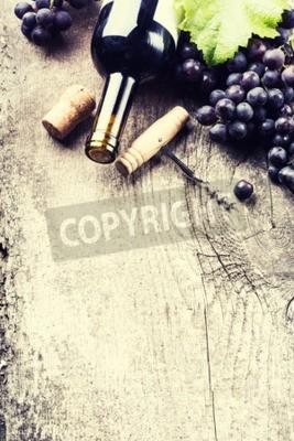 Fotomural Botella de vino oscuro, la uva y los corchos sobre fondo de madera vieja