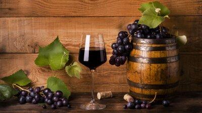 Fotomural Calice di vino rosso con uva e botte