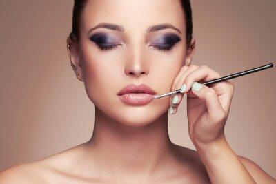 Fotomural Cara de mujer hermosa. Beauty girl with Perfect make-up.Makeup artista aplica lipstick.cosmetics