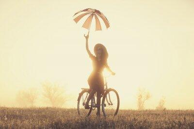 Fotomural Chica con paraguas en una bicicleta en el campo en tiempo de la salida del sol