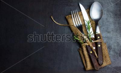 Fotomural Conjunto de cosecha rústica de cuchillería cuchillo, cuchara, tenedor. Fondo negro. Vista superior