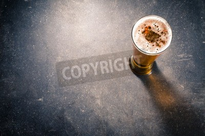 Fotomural Copa de cerveza en la mesa oscura