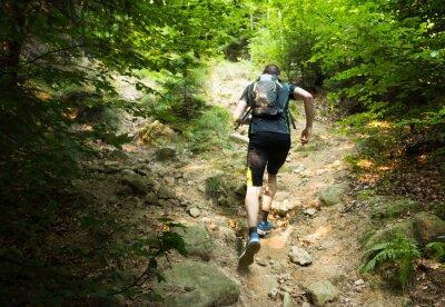Fotomural corredor de pista, con la mochila corriendo por la colina empinada
