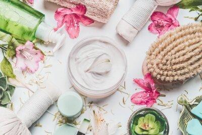 Fotomural Crema para la piel con pétalos de flores y otros productos cosméticos para el cuidado corporal y accesorios sobre fondo blanco, vista superior