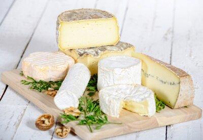 Fotomural diferente de queso con nueces sobre una tabla de madera blanca