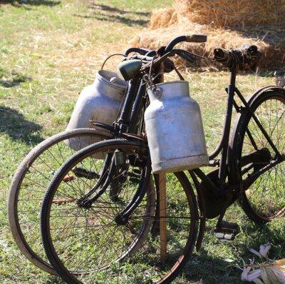 Fotomural Dos antiguas bicicletas oxidadas para el transporte de leche en la papelera