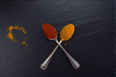 Fotomural Dos cucharas de la vendimia con las especias curry y paprika en fondo negro.