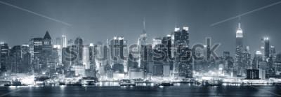 Fotomural El horizonte del centro de la ciudad de Nueva York Manhattan blanco y negro en la noche con los rascacielos se encendió en el río de Hudson con reflexiones.