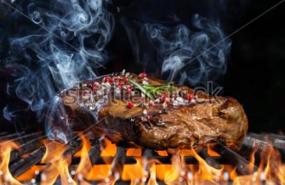 Fotomural Filete de ternera a la parrilla y fuego con fondo negro