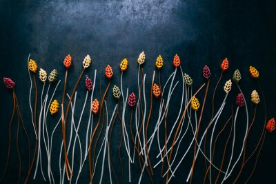 Fotomural flowers composition made out of colorful pasta on the dark  table, topview