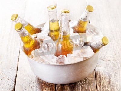 Fotomural Fría botellas de cerveza en el cubo con hielo en la mesa de madera