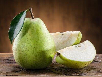 Fotomural Fruto de la pera con la hoja en fondo de madera.