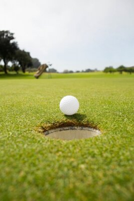 Fotomural Golf ball at the edge of the hole
