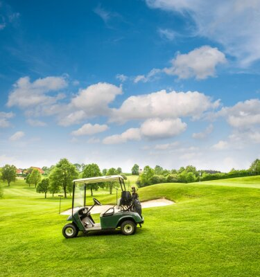 Fotomural Golf cart on a golf course. Green field and cloudy blue sky