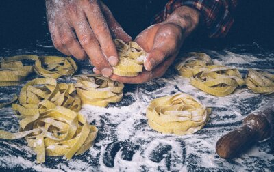 Fotomural Homemade uncooked pasta on black background. Making fresh italian fettuccine.