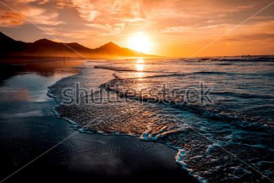 Fotomural Impresionante puesta de sol en la playa con un horizonte infinito y figuras solitarias en la distancia y increíbles olas espumosas. Colinas volcánicas en el fondo en colores cálidos idílicos.
