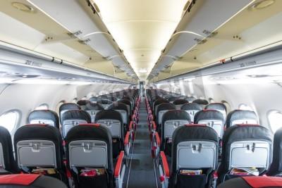Fotomural Interior moderno de la aeronave. Asientos negros y rojos dentro del avión. Fila de fuga simétrica de plazas en el interior del transporte aéreo. Clase turista de vuelo. Equipo para viajar. Plano ilumi