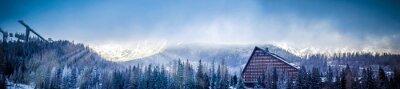 Fotomural Invierno panorámica vista panorámica de la montaña con un hotel y plataforma de salto de esquí, cubierto de nubes