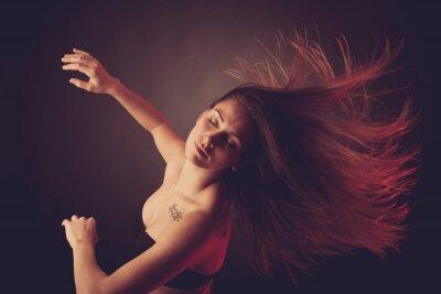 Fotomural Joven morena mujer caucásicos bailando y su pelo que fluye a través del aire
