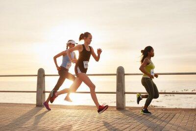 Fotomural Jóvenes mujeres corriendo en una carretera por el mar