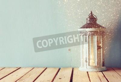 Fotomural La linterna de madera blanca de la vendimia con la vela ardiente y las ramificaciones de árbol en la tabla de madera. Imagen filtrada retro con el recubrimiento del brillo