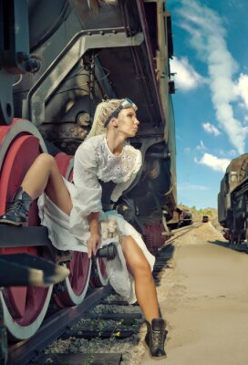Fotomural La mujer en el vestido de la vendimia se está sentando en la rueda de la locomotora.