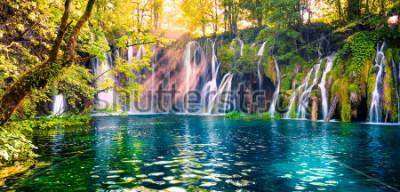 Fotomural La última luz del sol ilumina la cascada de agua pura en el Parque Nacional de Plitvice. Panorama colorido de la primavera del bosque verde con el lago azul. Gran vista al campo de Croacia, Europa.