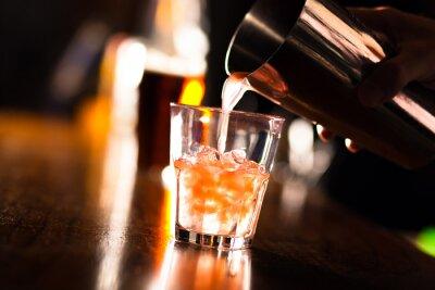 Fotomural Las manos de un camarero vierte una bebida en un vaso