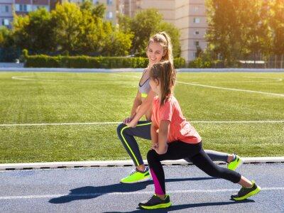 Fotomural Madre e hija pequeña están haciendo ejercicio en el estadio. Él