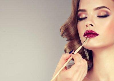 Fotomural Mano de maestro de maquillaje, labios de pintura de la joven modelo hermosa. Maquillaje en progreso.