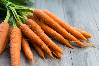 Fotomural Manojo de zanahorias frescas sobre fondo de madera