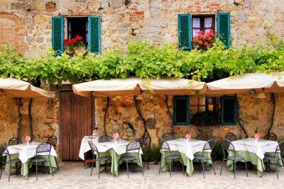 Fotomural Mesas de café y sillas fuera de un edificio de piedra en la Toscana