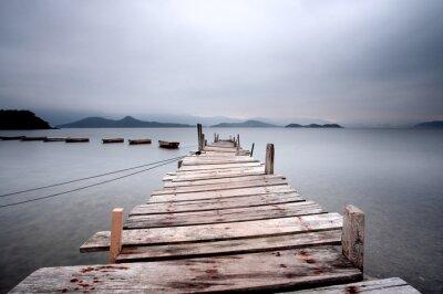 Fotomural Mirando sobre un muelle y un barco, de tono oscuro.