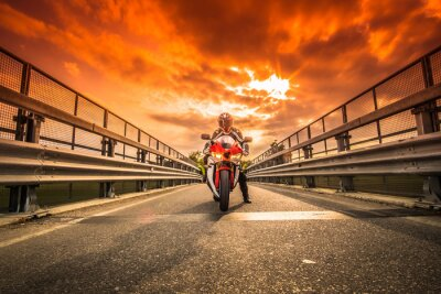 Fotomural Moto da strada pronta alla partenza sotto ONU cielo rosso al tramonto