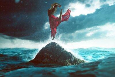 Fotomural Mujer baila en una roca en el mar
