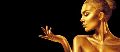 Fotomural Mujer de oro. Chica de modelo de moda de belleza con piel dorada, maquillaje, cabello y joyas sobre fondo negro. Retrato de arte de moda