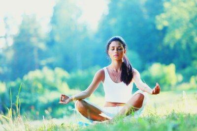 Fotomural Mujer joven haciendo ejercicios de yoga en el parque verde