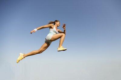 Fotomural Mujer joven que toma el salto de longitud
