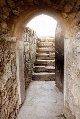 Fotomural Muro de piedra con la puerta abierta y los rayos de luz detrás