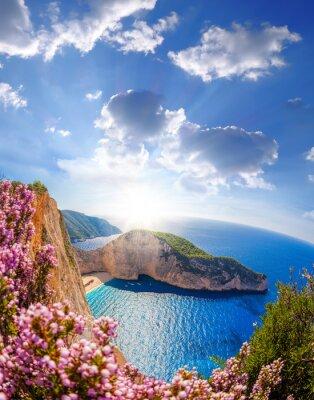 Fotomural Navagio playa con naufragio y flores contra la puesta del sol, isla de Zante, Grecia