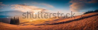 Fotomural Panorama de la puesta de sol en un valle de montaña de los Cárpatos con maravillosa luz dorada en una colina