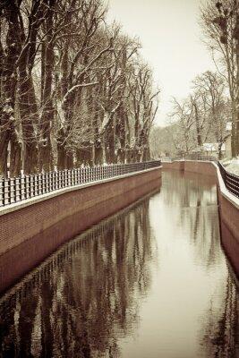 Fotomural Parque con río y terraplén cubierto de nieve