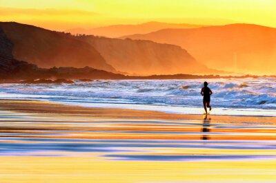 Fotomural persona corriendo en la playa al atardecer