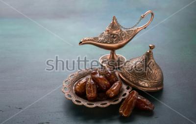 Fotomural Plaça de bronce con las fechas y la lámpara de Aladdin en fondo de madera verde oscuro. Ramadán de fondo. Ramadan Kareem.