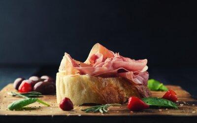 Fotomural Prosciutto con pan en una tabla de madera con aceitunas