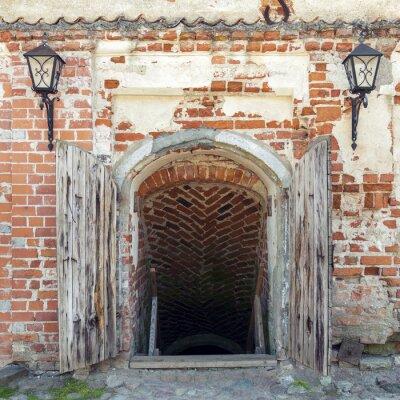 Fotomural Puertas abiertas de madera resistidas que conducen a la mazmorra de un viejo castillo