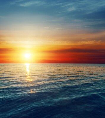 Fotomural puesta de sol rojo sobre el agua oscura
