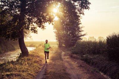 Fotomural Ragazzo all'alba corre che su strada de campo en la finca