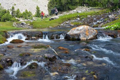 Fotomural Rapid and wide cascade river Fast moving water vivid rocky stones and group of people walking on green meadow on background