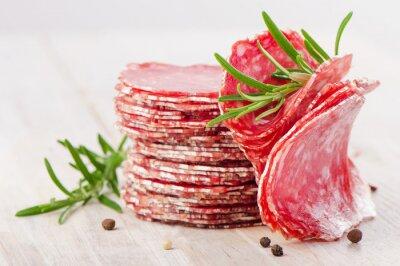 Fotomural Rebanadas de salami salchicha en una mesa de madera.